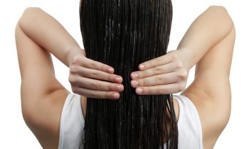 Young woman with coconut oil applied onto hair, on white backgro