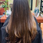 A woman with long hair sitting in Green Turtle Salon chair
