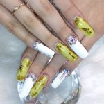A woman's nails designed with a green and white pattern